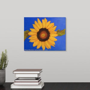 A painting of a Single sunflower & leaves on ultramarine blue background hanging over a black desk