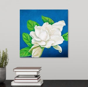 An original oil painting of a glowing white gardenia in full bloom, surrounded by a deep blue backdrop, hanging over a desktop