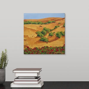 A painting of a sunburnt Sonoma, California hillside with yellow grasses, mixed with red roses and shrubbery, under a clear blue sky hanging over a black desk
