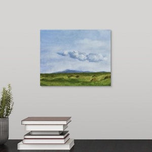 painting of a green springtime pasture in a Sonoma, California with rolling hills, billowing distant clouds, blue sky, and many piles of unwrapped hay laying in the abundant grasses hanging over a black desk