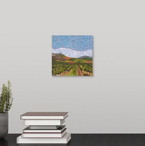 A painting of a foggy morning in Napa Valley California vineyard field with golden soil and green vines, flanked by hazy, distant hills hanging over a black desk