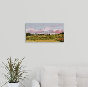 A painting of rosy-hued April clouds over a Marin County, CA meadow, filled with golden paths, green grasses, and orange California poppies hanging over a black desk
