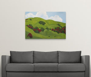 A landscape painting of lush green hillsides of Sonoma County, California in the winter rainy season. The painting includes dark green shrubs blooming with red flowers and two horses feeding on the green grass on a white wall over with a grey couch