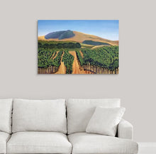 Load image into Gallery viewer, A painting of green and golden, sunlit vineyard hillsides of Napa Valley, California in the fall hanging on a white wall over a white couch