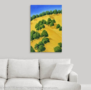 A painting of sunlit trees on the golden hillside that surrounding Lake Berryessa in the Napa Valley, California in summertime hanging on a white wall over a white couch