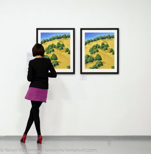 Two Paintings of sunlit trees on the golden hillside that surrounding Lake Berryessa in the Napa Valley, California in summertime hanging on a gallery wall with art patron