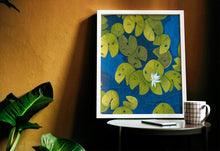 Load image into Gallery viewer, A deep blue & aqua blue pond with floating golden yellow lily pads and white flower blooms painting leaning on a yellow wall
