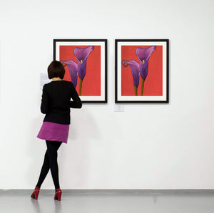 Two Purple Calla Lilies in full bloom with a red backdrop paintings in an art gallery with patron viewing