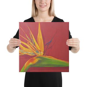 A canvas print of a painting, by fine artist Nancy McLennon, of a green, yellow and purple Bird of Paradise flower on a rust red background, being held by a woman.