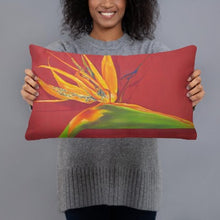 Load image into Gallery viewer, A printed decorative pillow with the image of painting, by fine artist Nancy McLennon, of a green, yellow and purple Bird of Paradise flower on a rust red background being held by a woman.