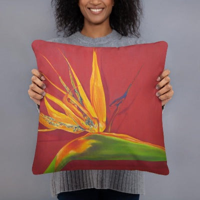 A printed decorative pillow with the image of painting, by fine artist Nancy McLennon, of a green, yellow and purple Bird of Paradise flower on a rust red background being held by a woman.