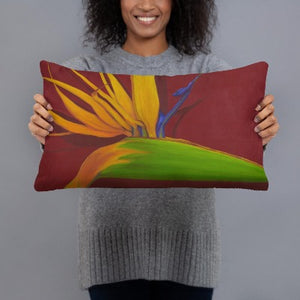 A printed, decorative pillow with the image of painting, by fine artist Nancy McLennon, of a green, yellow and purple Bird of Paradise flower on a dark red background being held by a woman.