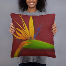 Load image into Gallery viewer, A printed, decorative pillow with the image of painting, by fine artist Nancy McLennon, of a green, yellow and purple Bird of Paradise flower on a dark red background being held by a woman.