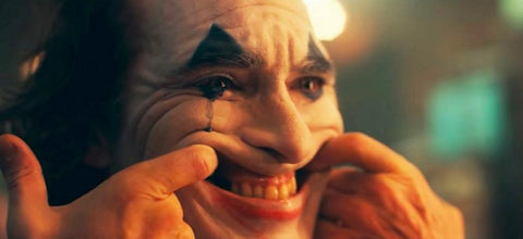 Image of Joaquin's Joker Performance. The Joker sticks two fingers in his mouth to force a comedic smile.