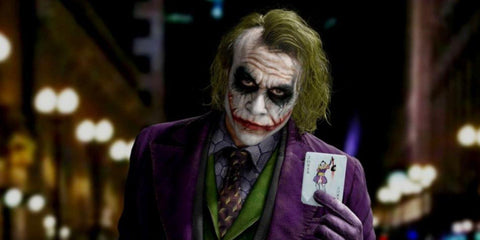Image of Heath Ledgers Joker, holding the Joker card.