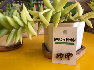 "Wee laser cute earrings in the shape of mushrooms are attached to a white backing card that says ""World of Whimm."" They are leaning against a small succulent plant on a bright yellow table."