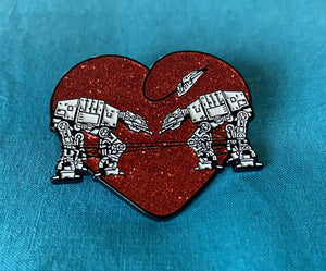 A red glitter enamel pin of two AT-AT's being tied with a rope that is in the shape of a heart. Background is aqua blue.