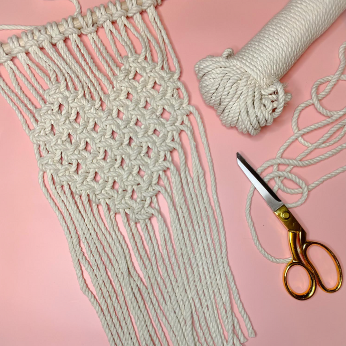 Image of a macrame wall hanging made out of white rope. The center of the piece forms a heart. There is a pair of scissors and macrame cord to the right side. The background is light pink.