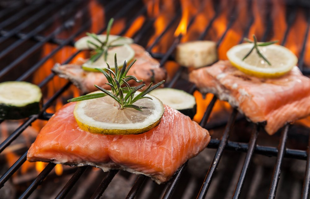 Fresh fish on the grill with lemons and herbs for seasoning