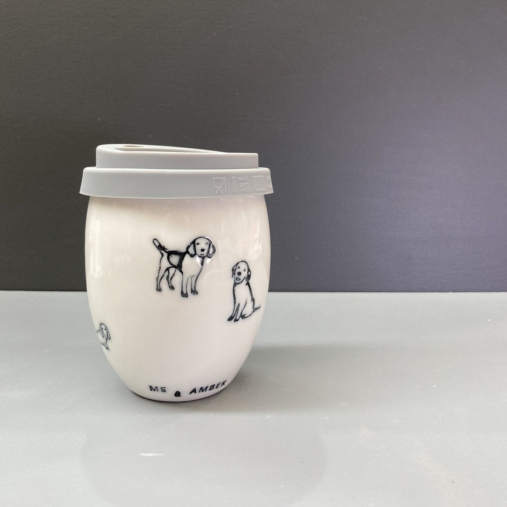 A white hand made ceramic keep cup. Stamped with a black dog and puppy print and a clear glaze. The cup has a grey silicone lid. A design collaboration between Hayden Youlley and Me and Amber