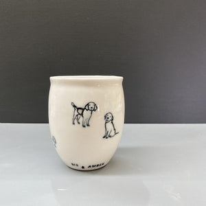 A white hand made ceramic keep cup. Stamped with a black dog and puppy print and a clear glaze. A design collaboration between Hayden Youlley and Me and Amber
