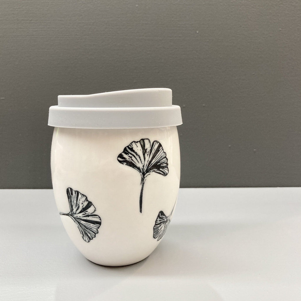 A hand made white ceramic keep cup. Stamped with a black ginkgo leaf print. The cup has a glazed exterior finish with a grey silicone lid. A design collaboration between Hayden Youlley and Feloffa