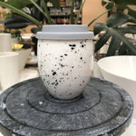 A clean modern ceramic keep cup. Has an egg like shape. The cup is white hand made ceramic and hand painted with black speckles