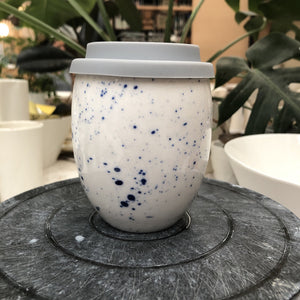 A clean modern ceramic keep cup. Has an egg like shape. The cup is white hand made ceramic and hand painted with blue Speckles