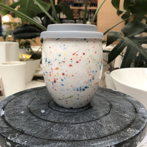 A clean modern ceramic keep cup. Has an egg like shape. The cup is white hand made ceramic and hand painted with rainbow speckles