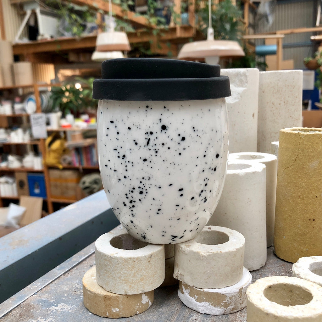 A clean modern ceramic keep cup. The cup Resembles an egg shape. The Good Egg keep cup is hand made in white ceramic and hand painted with black speckle.