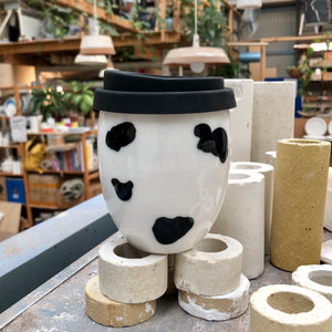A clean modern ceramic keep cup. The cup Resembles an egg shape. The Good Egg keep cup is hand made in white ceramic and hand painted with a cow print.
