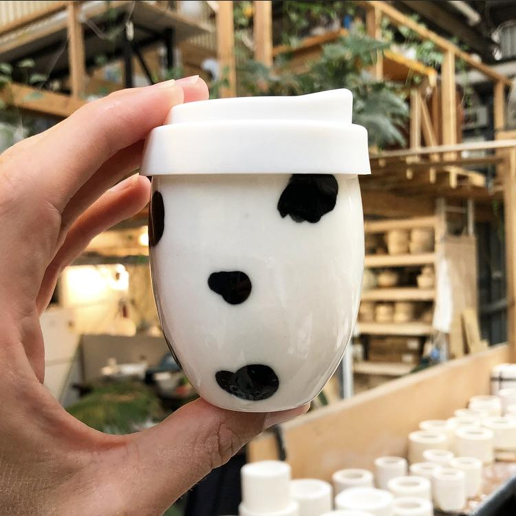 A white ceramic piccolo keep cup. The little cup resembles a timeless egg shape. The Good Egg keep cup is hand made in white Imperial porcelain and hand painted with a cow print