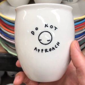 "A white ceramic hand made keep cup. Stamped in black with the words ""do not approach"". A design collaboration between Hayden Youlley and Gimme Space"
