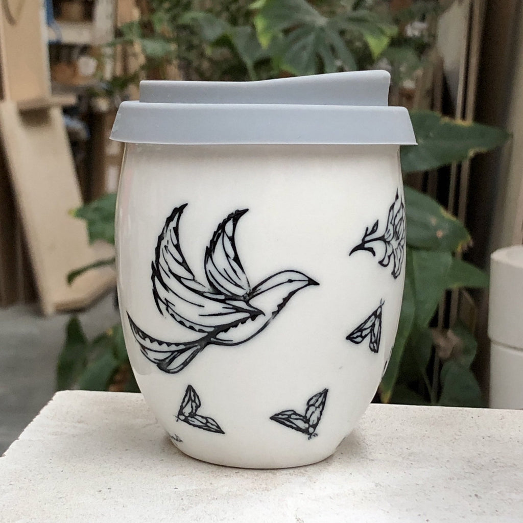 A beautiful white ceramic hand made keep cup. Stamped with a spring time inspired drawing, that is filled with birds flowers and moths. The cup is stamped in black with a clear glaze. A design collaboration between Hayden Youlley and Renata Sàfadi