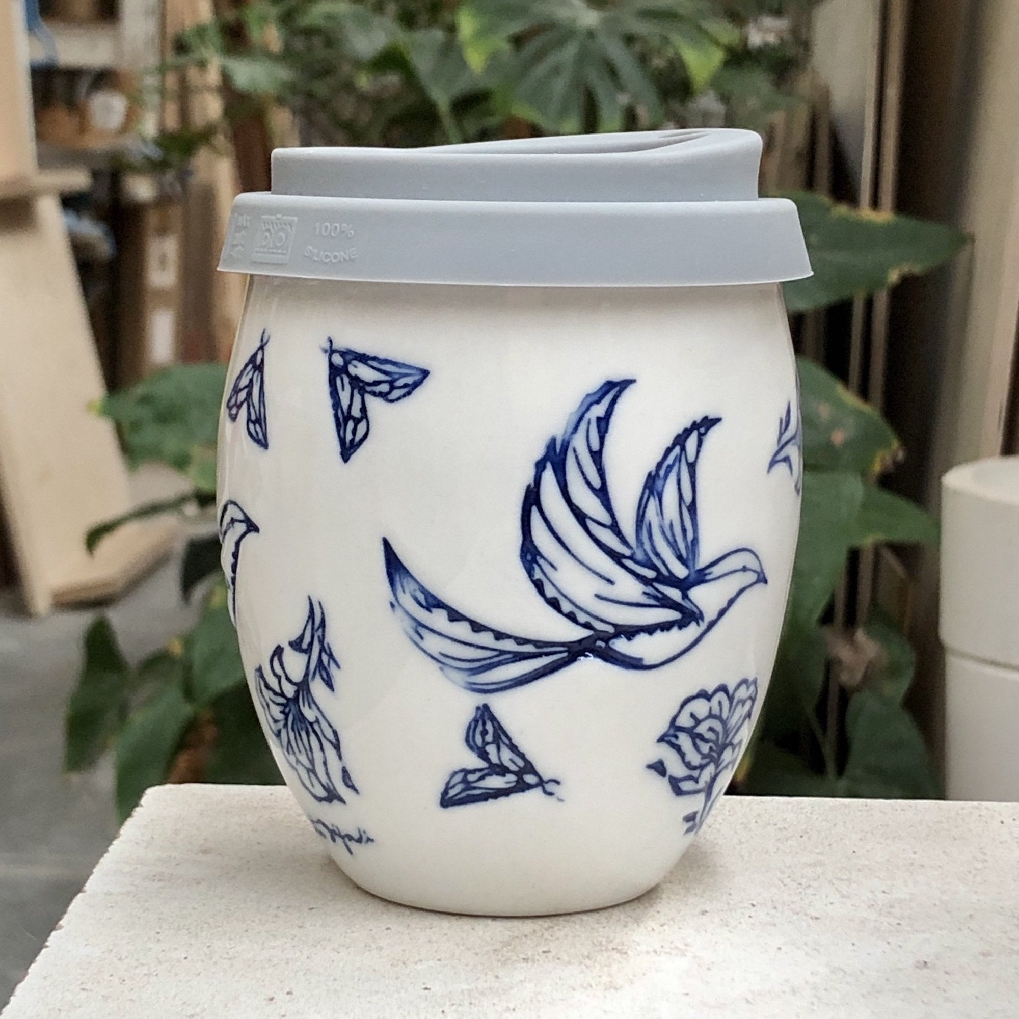 A beautiful white ceramic hand made keep cup. Stamped with a spring time inspired drawing, that is filled with birds flowers and moths. The cup is stamped in blue with a clear glaze. A design collaboration between Hayden Youlley and Renata Sàfadi