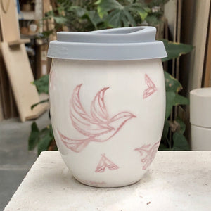 A beautiful white ceramic hand made keep cup. Stamped with a spring time inspired drawing, that is filled with birds flowers and moths. The cup is stamped in pink with a clear glaze. A design collaboration between Hayden Youlley and Renata Sàfadi