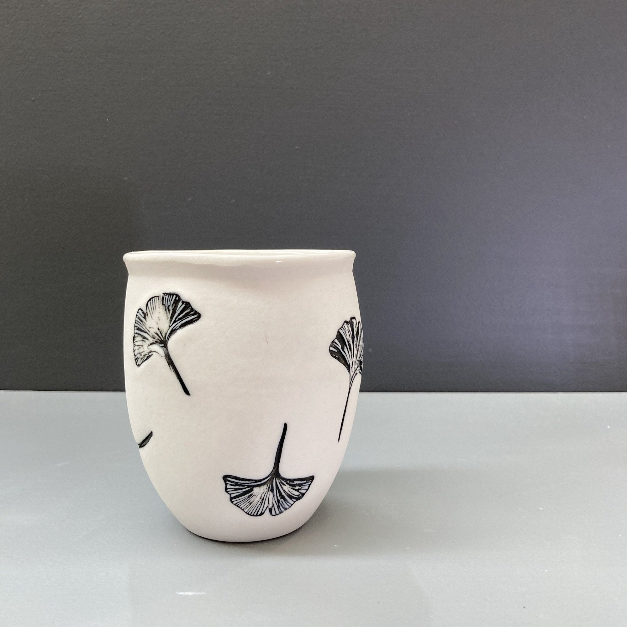 A hand made white ceramic keep cup. Stamped with a black ginkgo leaf print. The cup has an unglazed  matte finish. A design collaboration between Hayden Youlley and Feloffa