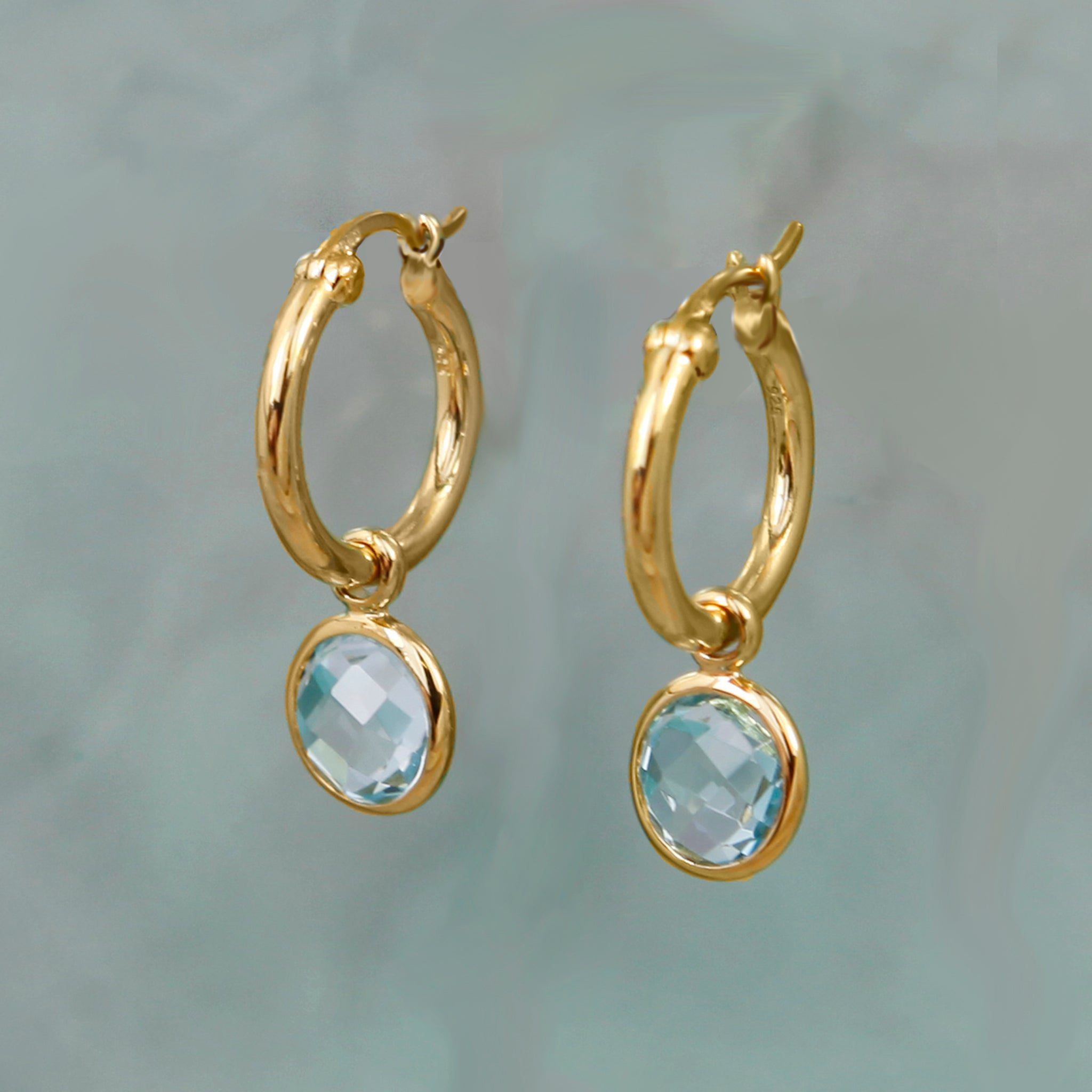 Staged Shot of Gold and Blue Topaz Huggie Hoop Earrings