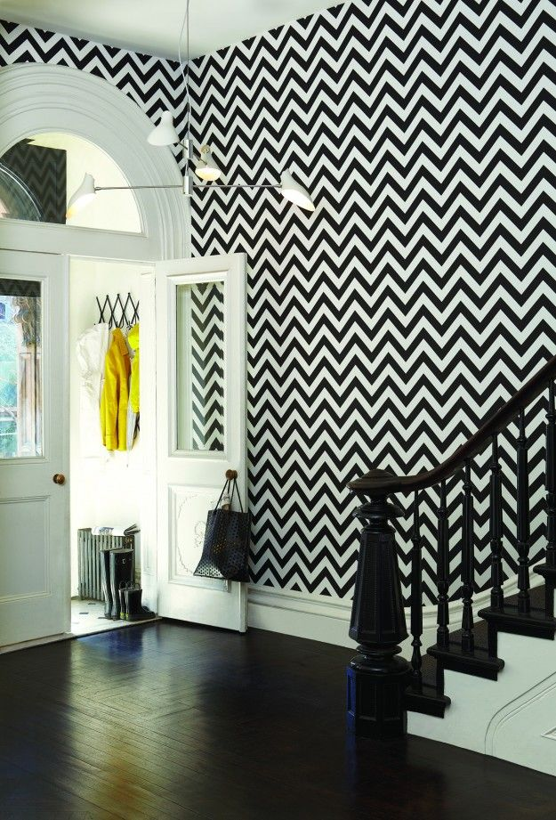 Soaring, bright home entry with white French doors, curved transom, dark hardwood floors, black and white chevron wallpaper