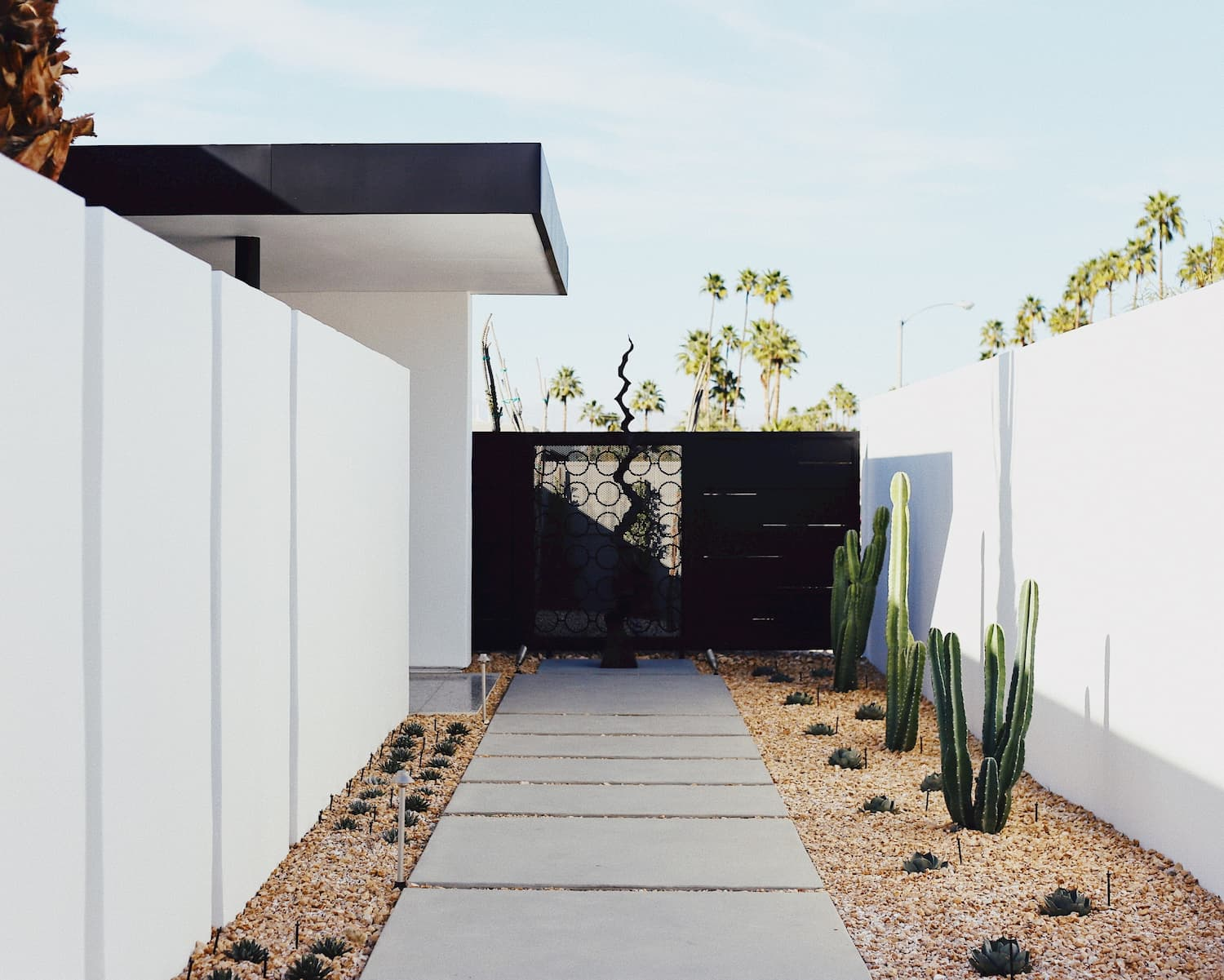 Southwestern-style courtyard features white stone walls and eco-conscious landscaping of rock and cacti