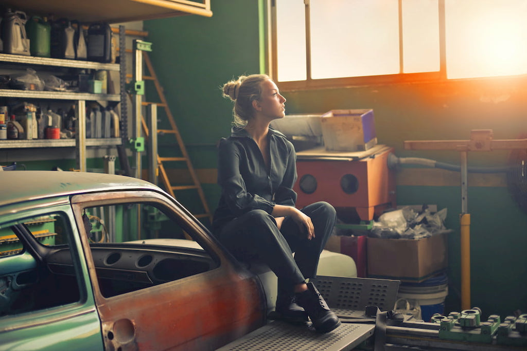 Woman sitting on old car in garage, cluttered wood shelves behind her to organize