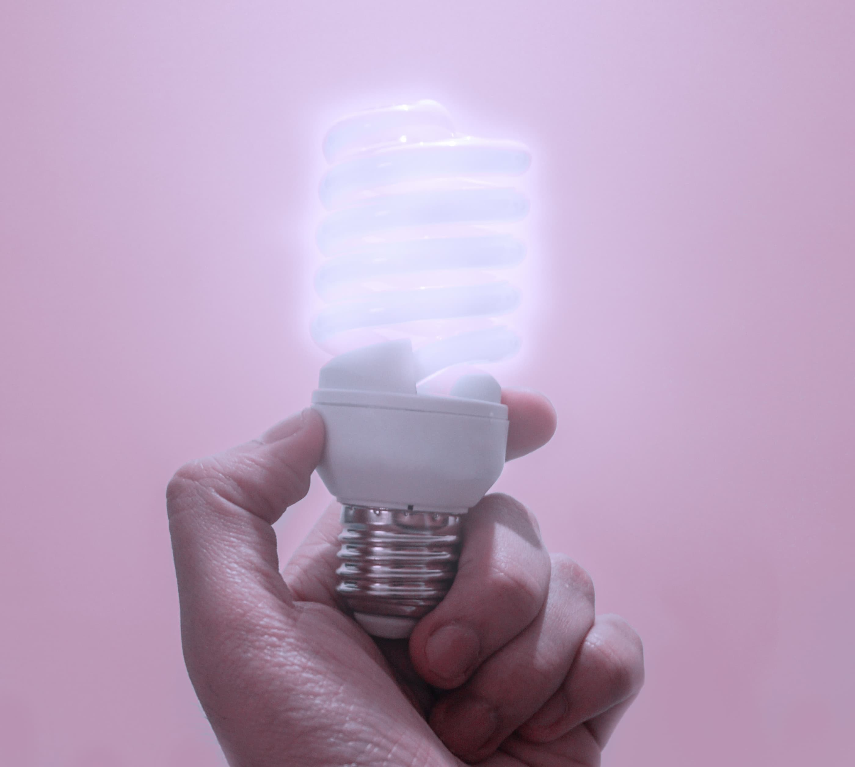Closeup of hand holding eco-conscious LED light against soft pink background