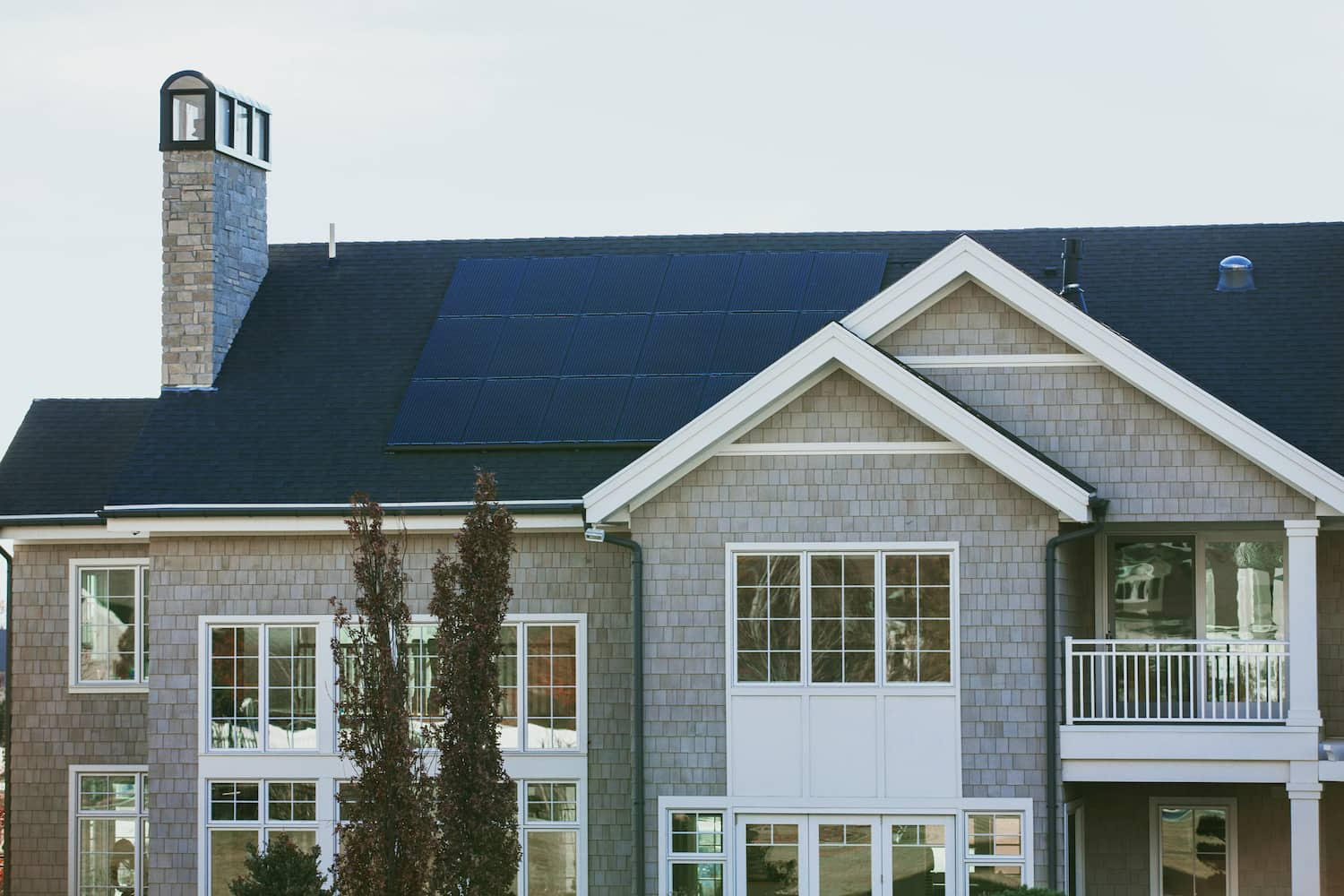 Eco-conscious solar panels on tile roof of modern coastal-style home