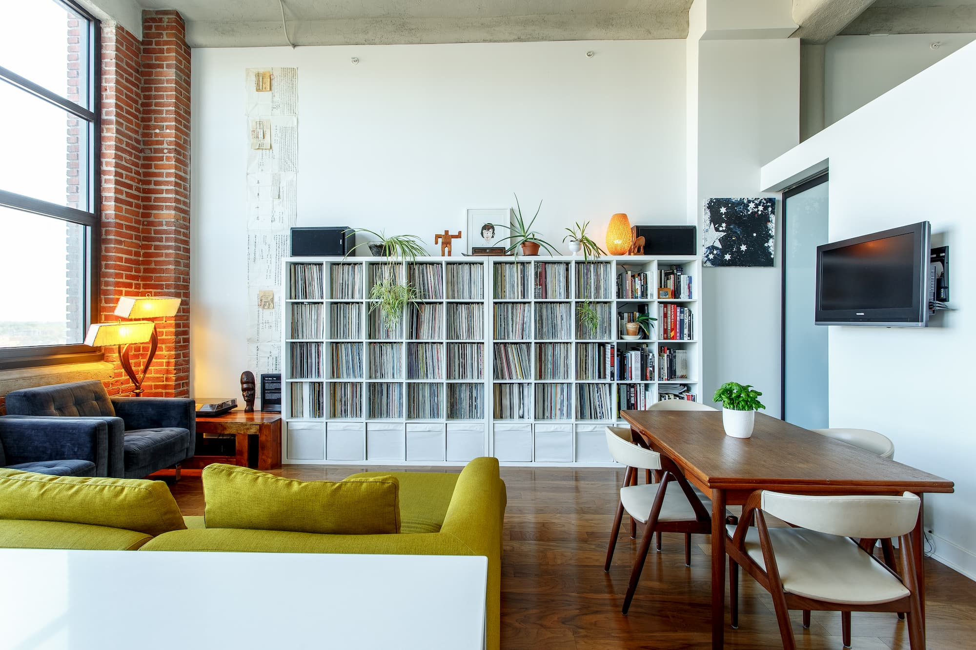 Well-maintained corner in industrial living room styled with eclectic furniture and décor elements, pops of bright color
