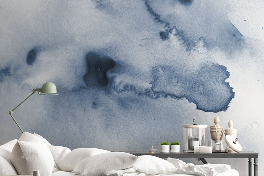 Mural-like watercolor wallpaper featuring vivid blue and white sky backs soft white pillow-back sofa