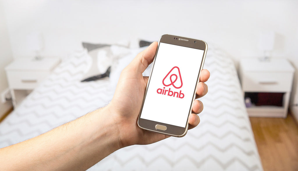Closeup of hand holding smartphone displaying Airbnb logo on screen, bedroom styled in whites and greys in background