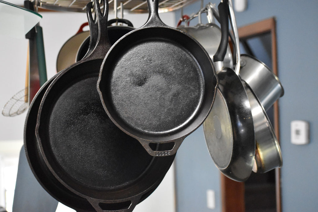 Cast iron skillets hang from a rack