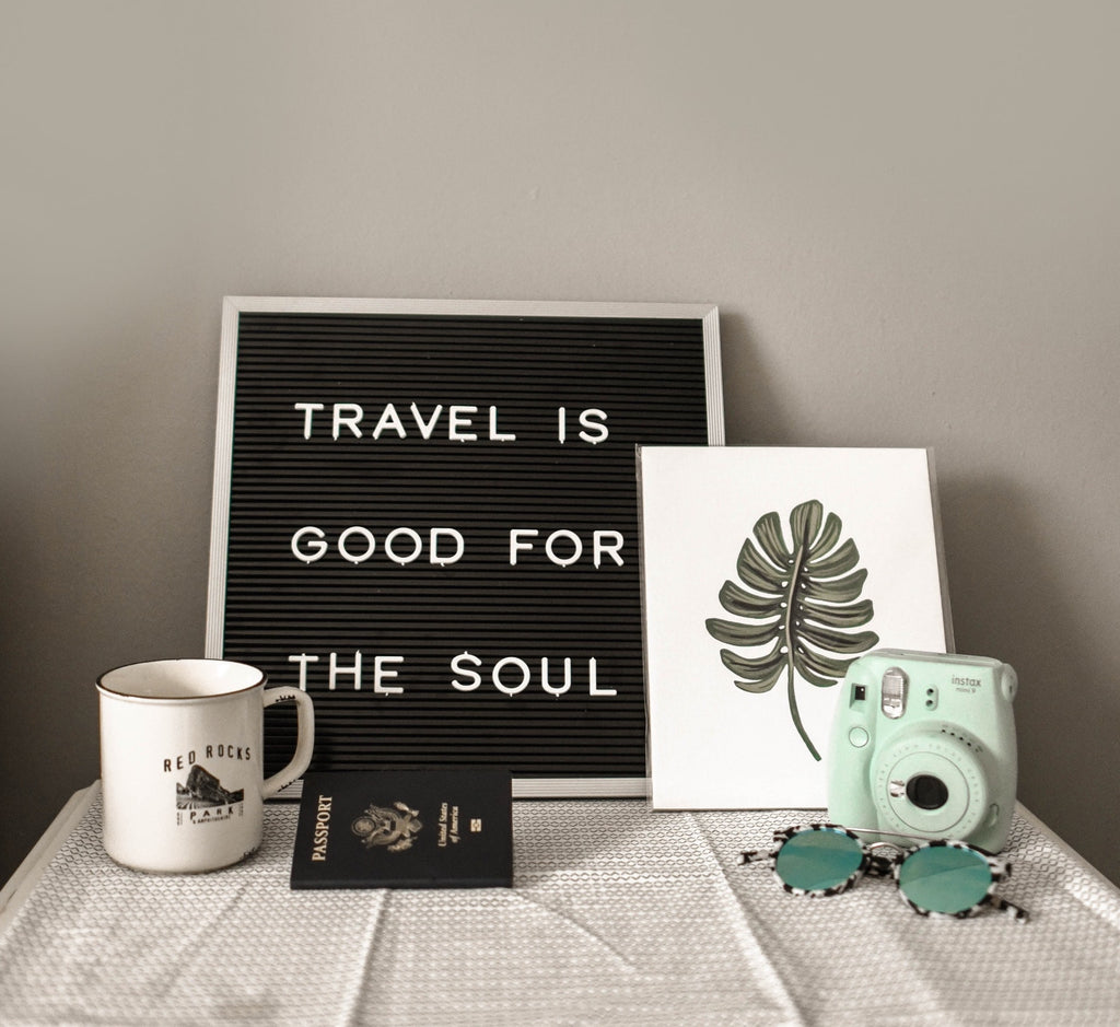 "Closeup of camping mug, passport, décor items, lettered sign behind says ""Travel is good for the soul"""