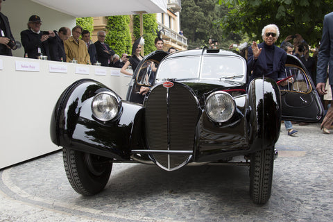 crowd look on as a black  Bugatti Type 57CS Atlantic is presented