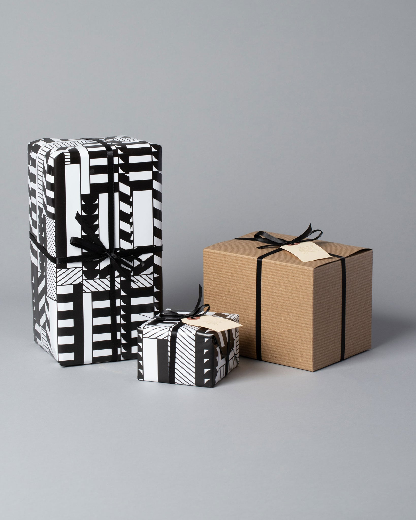 Gift Wrapping options, of black and white printed wrapping paper and cardboard boxes all wrapped with ribbon
